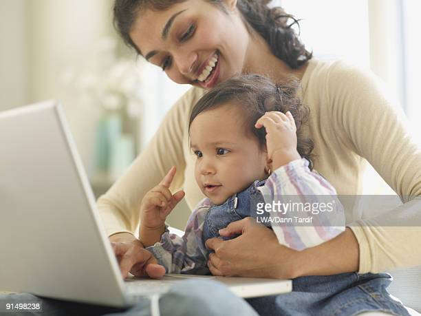 Hispanic mother and baby looking at laptop