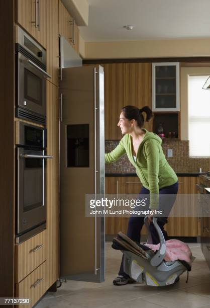 Hispanic mother and baby looking in refrigerator