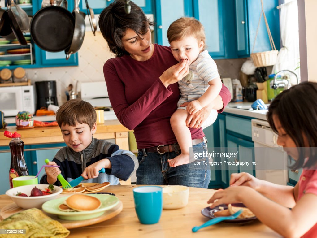 Hispanic mother and children having breakfast : Stock Photo