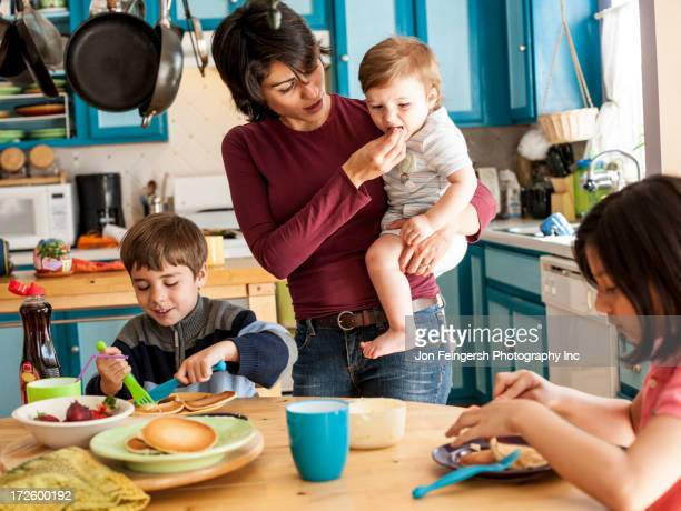 Hispanic mother and children having breakfast