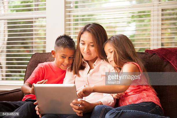 Hispanic mother and children learn on digital tablet at home.