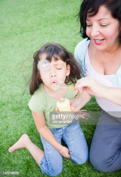 Hispanic mother and daughter blowing bubbles