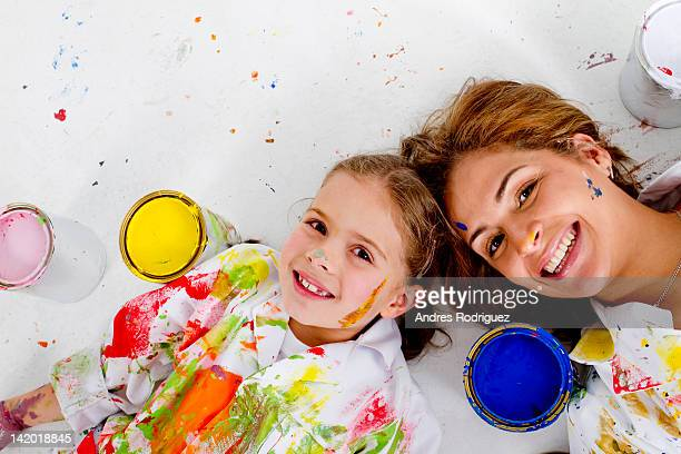 Hispanic mother and daughter covered in paint laying on floor