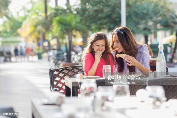 Hispanic mother and daughter eating at cafe