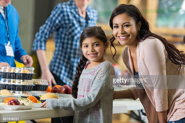 Hispanic mother and daughter eating meal at community food bank