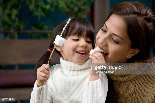 Hispanic mother and daughter eating roasted marshmallows