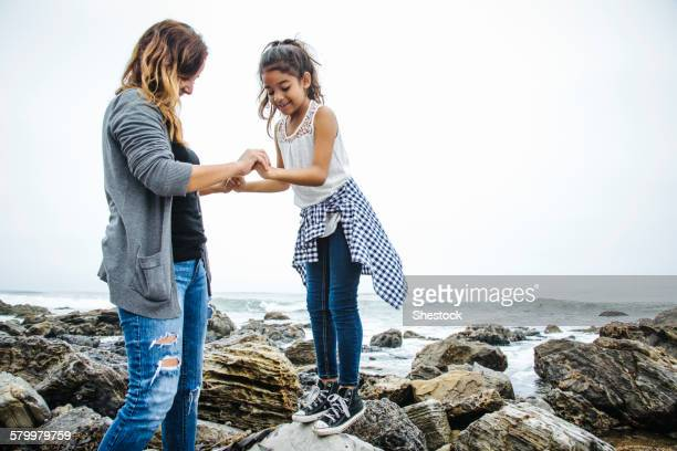 Hispanic mother and daughter exploring tide pools