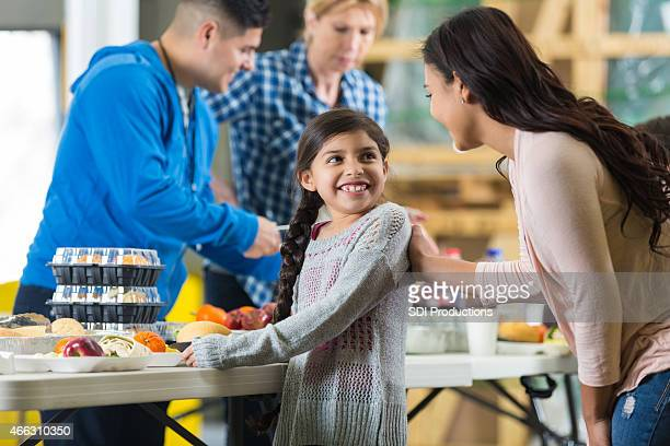 Hispanic mother and daughter having meal in food bank warehouse
