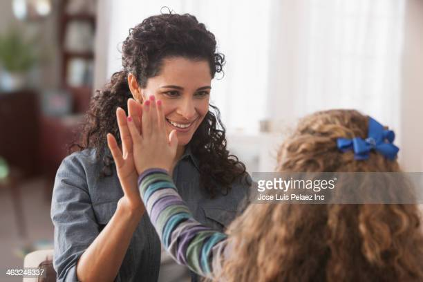 Hispanic mother and daughter high fiving
