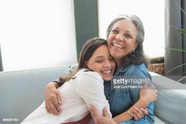 Hispanic mother and daughter hugging on sofa