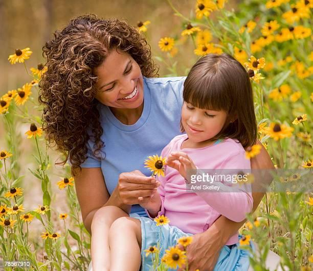 hispanic mother and daughter in flower patch - depilazione intima foto e immagini stock