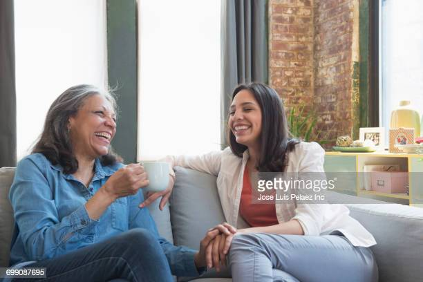 Hispanic mother and daughter laughing on sofa