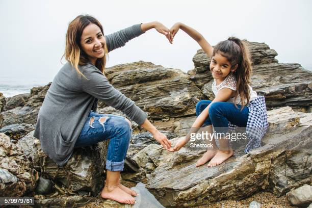 Hispanic mother and daughter making heart shape in tide pools