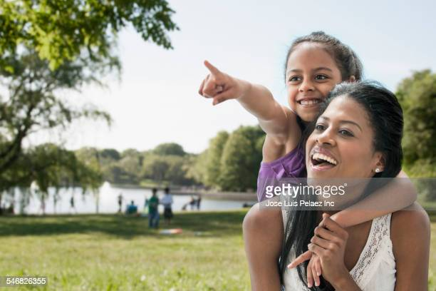 Hispanic mother and daughter playing in park