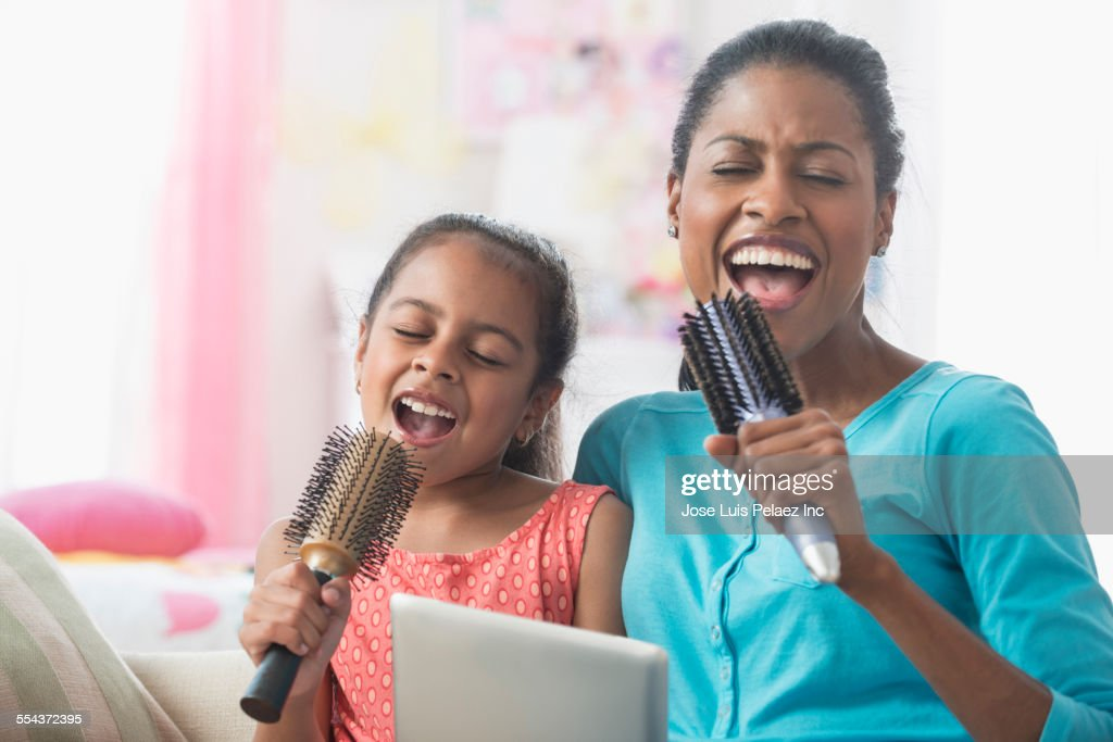 Hispanic mother and daughter singing with hairbrushes and digital tablet : Stock Photo
