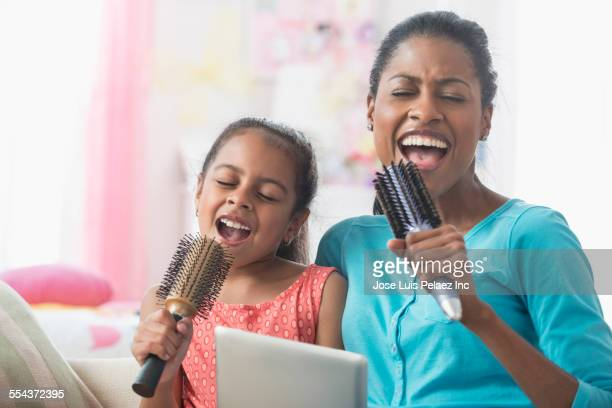 hispanic mother and daughter singing with hairbrushes and digital tablet - chanter photos et images de collection