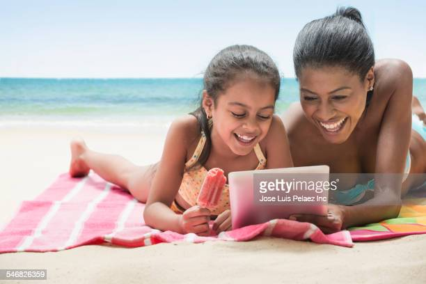 hispanic mother and daughter using digital tablet on beach - mother daughter towel stock photos and pictures