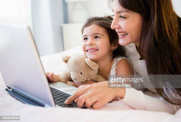 Hispanic mother and daughter using laptop together