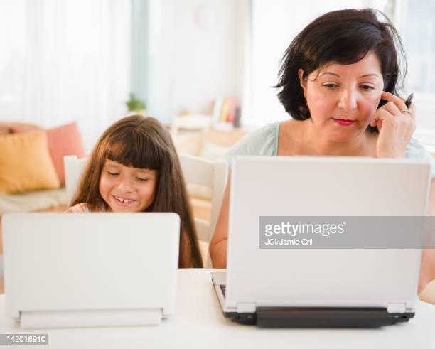 hispanic mother and daughter using laptops - anonymous fotografías e imágenes de stock