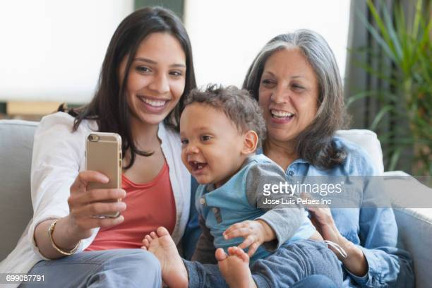 Hispanic mother and grandmother posing for cell phone selfie with baby boy