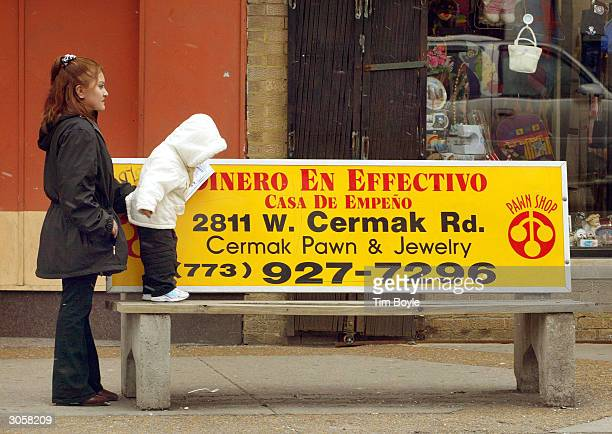 Hispanic mother and her daughter wait for a bus near a promotional bench March 9 2004 in Chicago's largely Hispanic Little Village neighborhood The...