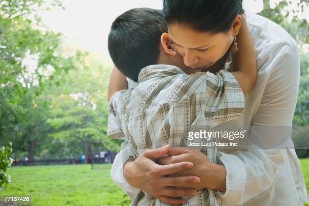hispanic mother and son hugging - sad mom stock pictures, royalty-free photos & images