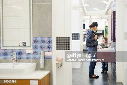 salesman talking to hispanic family in bathroom supply store stock
