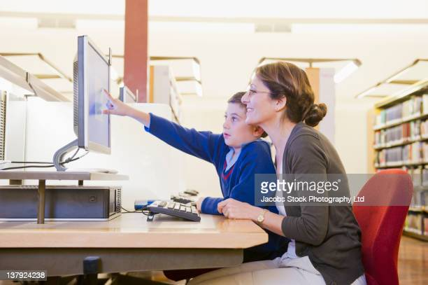 Hispanic mother and son using computer in library