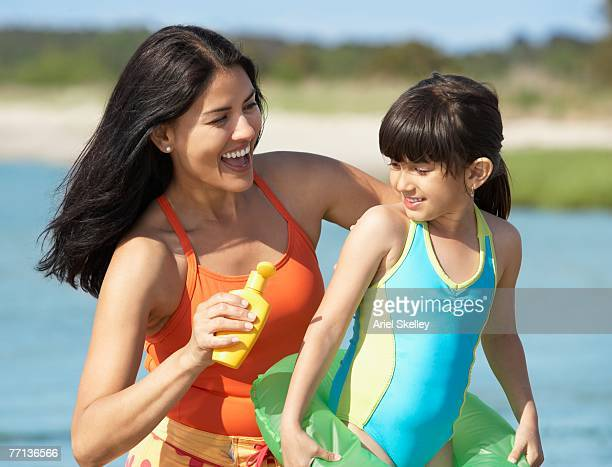 Hispanic mother applying sunscreen on daughter