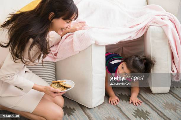 hispanic mother bringing daughter cookies in fort - fortress stock pictures, royalty-free photos & images