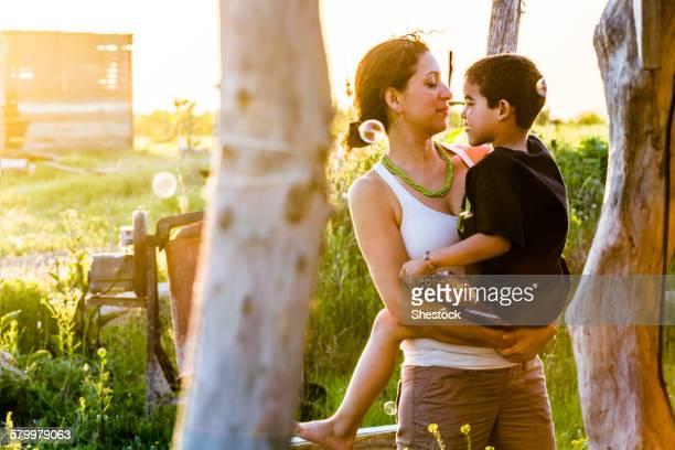 Hispanic mother carrying son in garden