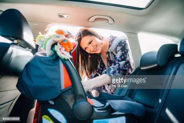 Hispanic mother fastening car seat in car