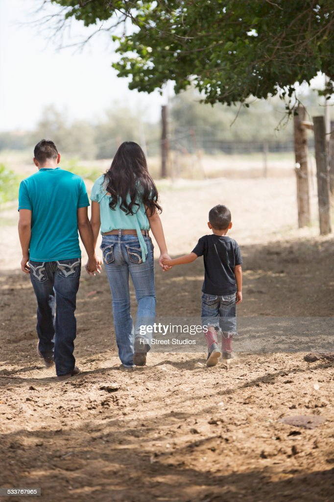 Hispanic mother, father and son walking on ranch : Foto stock