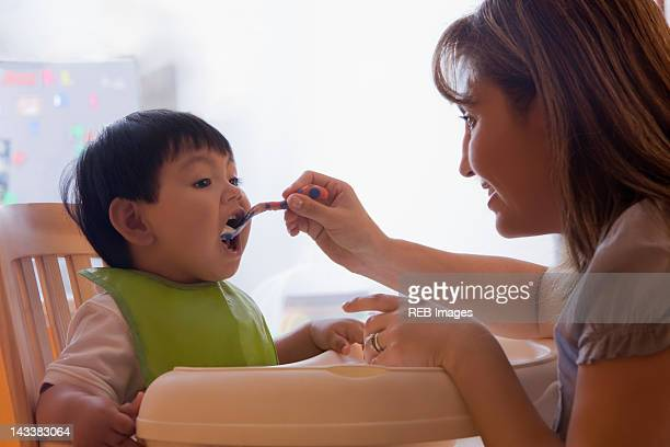 Hispanic mother feeding baby boy