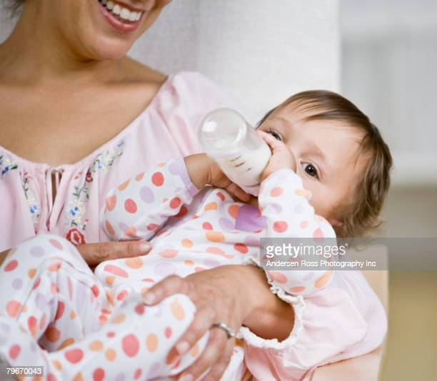 Hispanic mother feeding baby