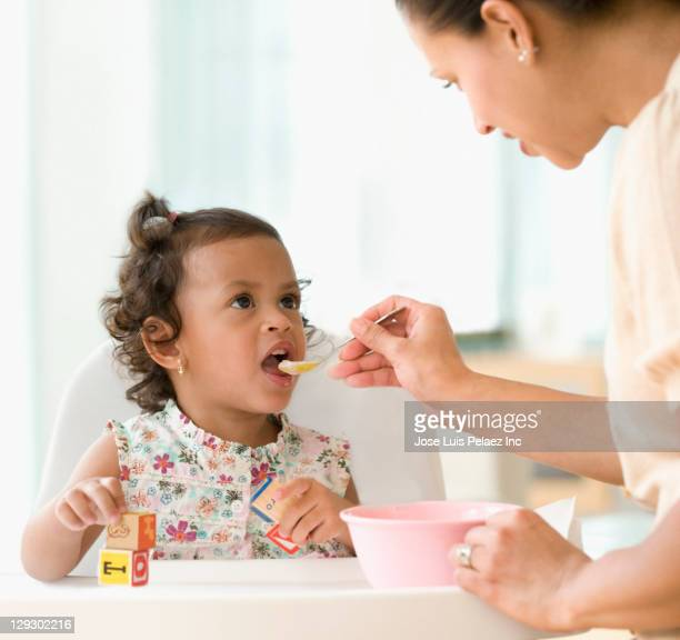 Hispanic mother feeding daughter
