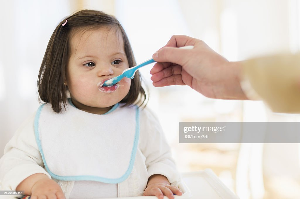 Hispanic mother feeding toddler in high chair : Stock Photo