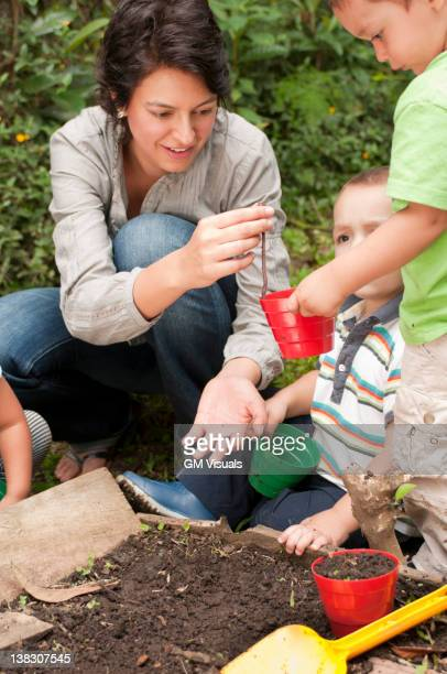 Hispanic mother gardening with sons