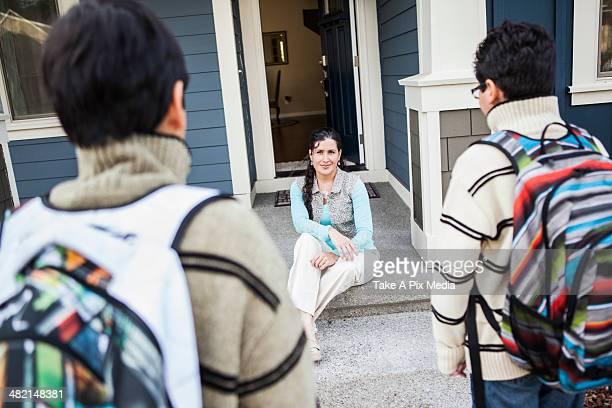 Hispanic mother greeting sons at door