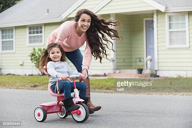 Hispanic mother helping daughter ride tricycle