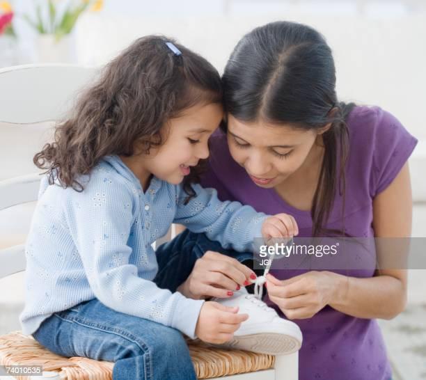 Hispanic mother helping daughter tie shoe
