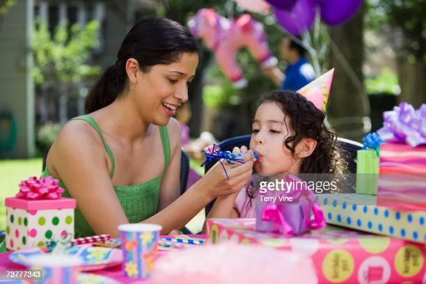Hispanic mother helping daughter with noisemaker at outdoor birthday party