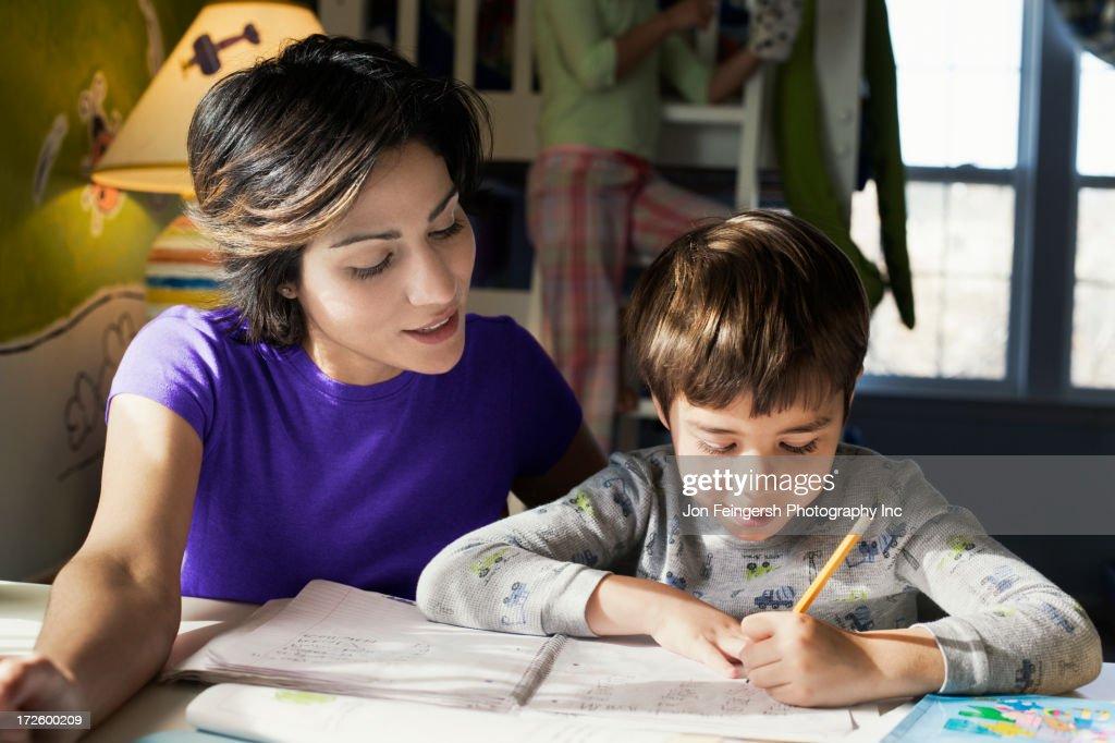 Hispanic mother helping son with homework : Stock Photo