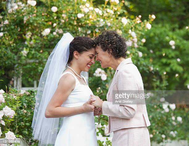 Hispanic mother holding hands with bride