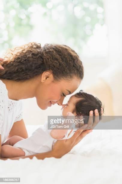 Hispanic mother holding infant on bed