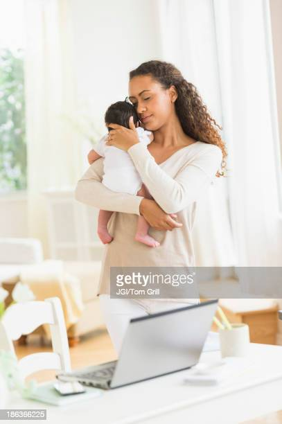 Hispanic mother holding infant son