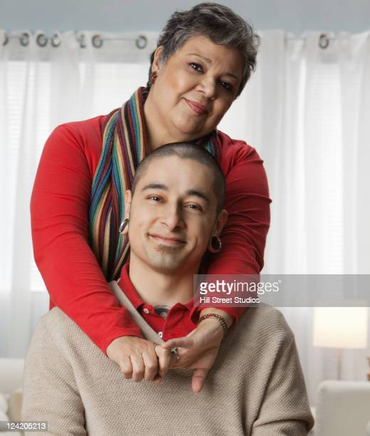 hispanic mother hugging adult son - earlobe stock photos and pictures
