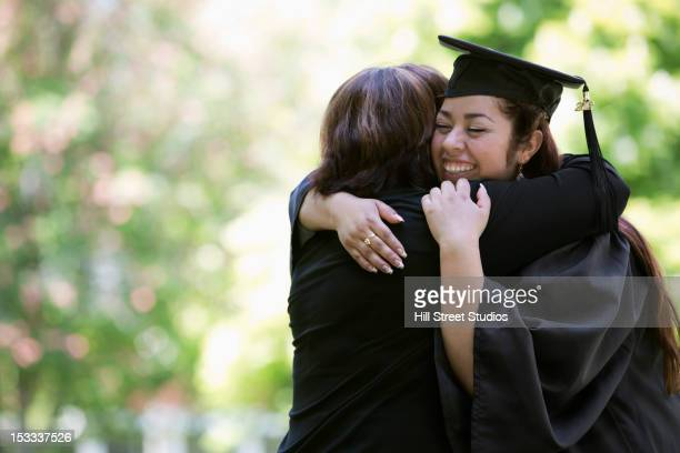 Hispanic mother hugging college graduate daughter