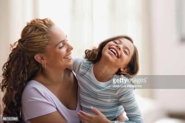 hispanic mother hugging laughing daughter - human body part - fotografias e filmes do acervo