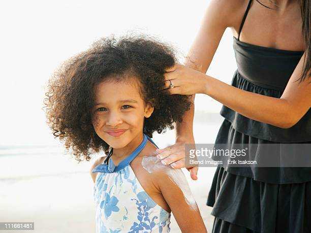 hispanic mother rubbing sunscreen on daughter at beach - sunscreen stock photos and pictures